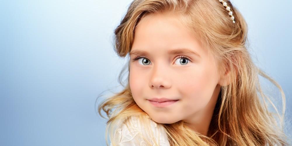 Portrait eines kleinen Mädchens mit langen blonden Haaren und Perlenschmuck im Haar, blauer Hintergrund