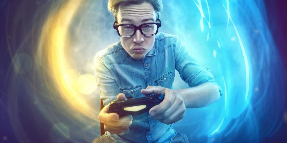 Junger Mann mit Jeanshemd und Nerdbrille beim Zocken am Gamecontroller, abstrakter Hintergrund