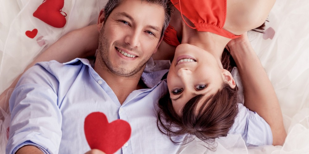 Junges Paar liegt auf dem Bett und hält ein rotes Herz hoch