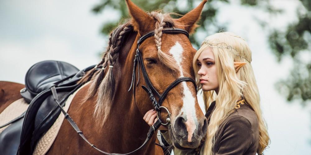 Blonde Elfenfrau mit spitzen Ohren steht an ihrem Pferd