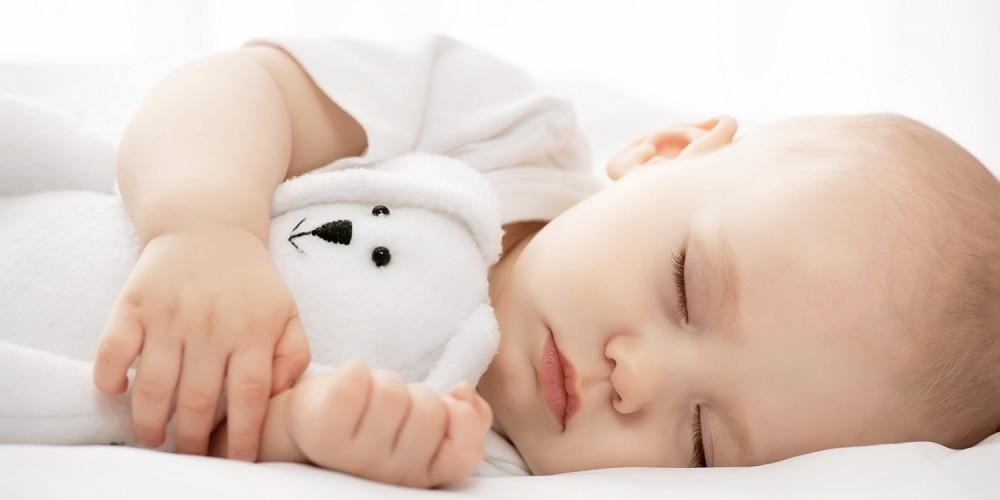 Baby liegt friedlich schlafend im Bett und hält ein weißes Kuscheltier in den Armen