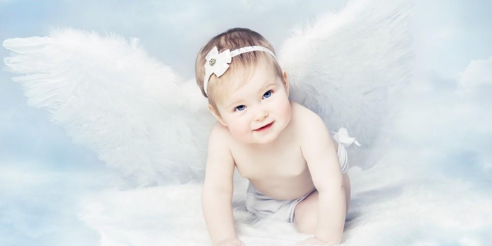 Baby mit weißem Haarreif und Flügeln als Engel verkleidet vor blauem Wolkenhintergrund