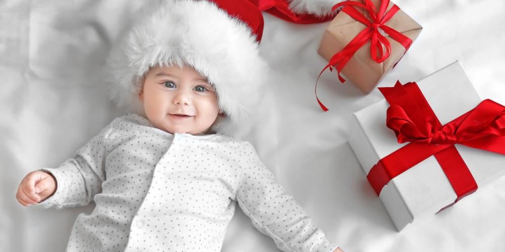 Baby in gepunktetem Schlafanzug liegt mit Weihnachtsmütze auf einer weißen Decke neben Geschenken mit roter Schleife