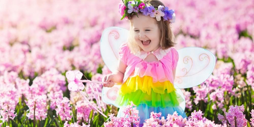Kleines Mädchen ist als bunte Fee verkleidet und steht mit ihrem Feenstab in einem pinken Blumenfeld