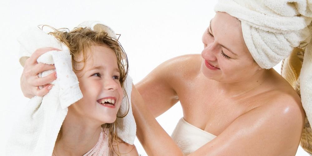 Mutter und Tochter nach Bad in Handtücher gewickelt, Mutter trocknet Tochter die Haare