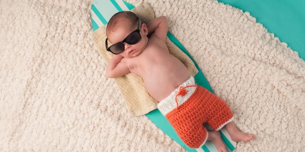 Baby mit Sonnenbrille auf Surfbrett