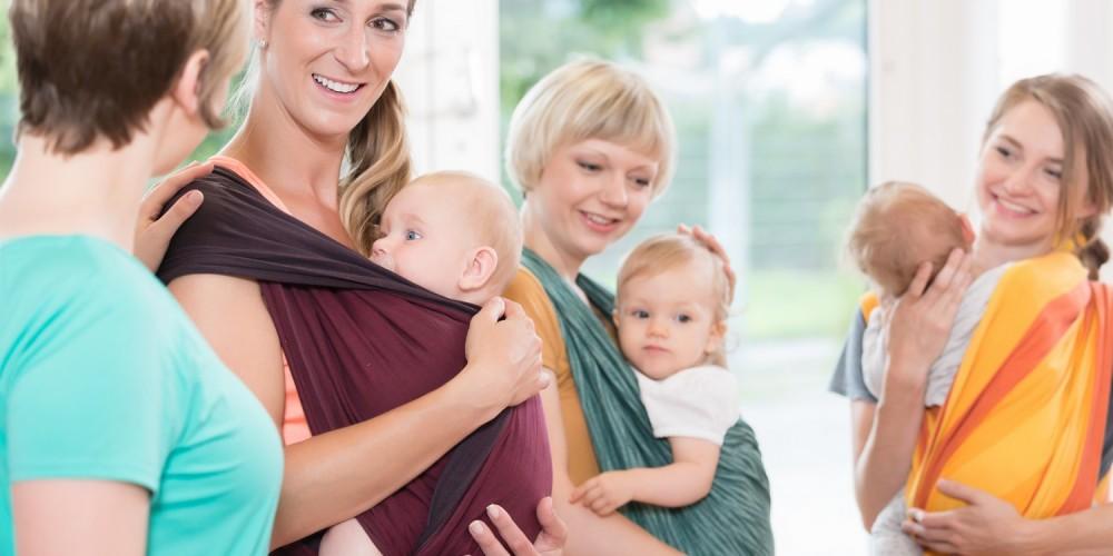 Junge Frauen mit ihren Babys in einer Krabbelgruppe, die Kinder in Tragetücher gebunden