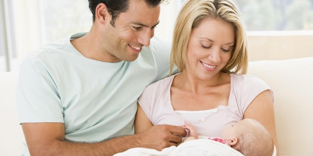Junge Eltern mit Neugeborenem auf Couch