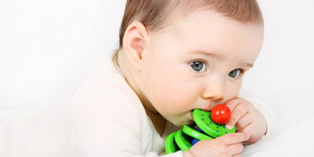 Dunkelhaariges Baby nuckelt an einem grünen Holzspielzeug für Babys