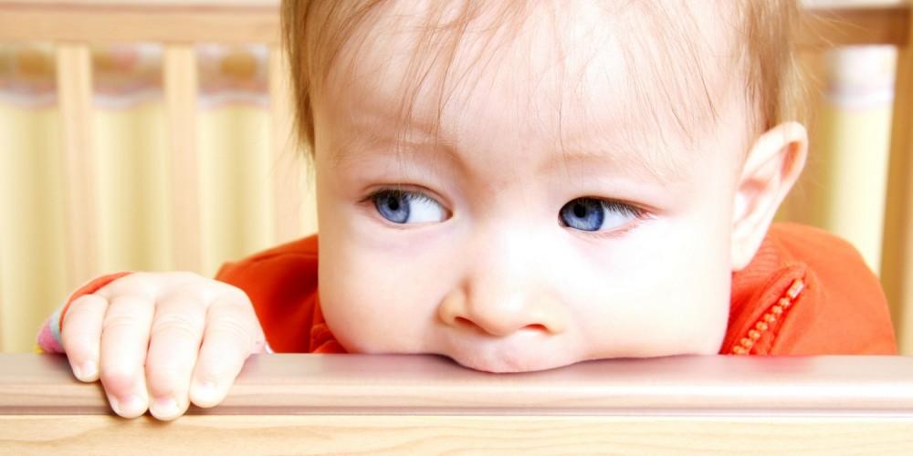 Baby beißt in das Geländer eines Laufstalls