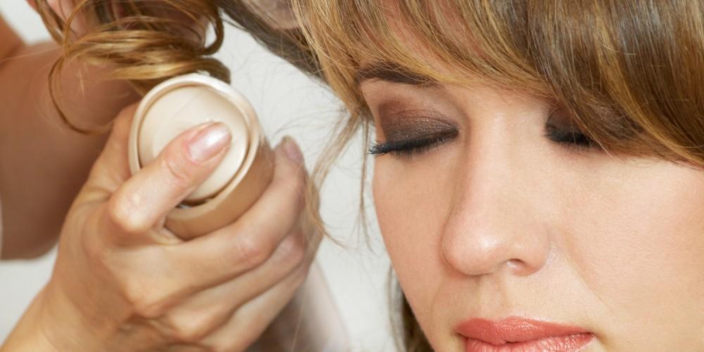Frau benutzt Haarspray