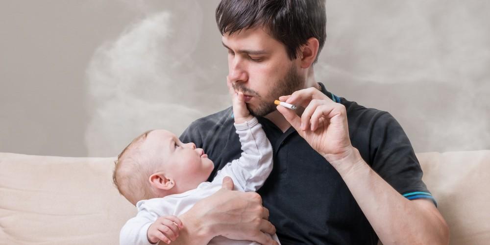 Rauchender Vater mit Baby auf dem Arm