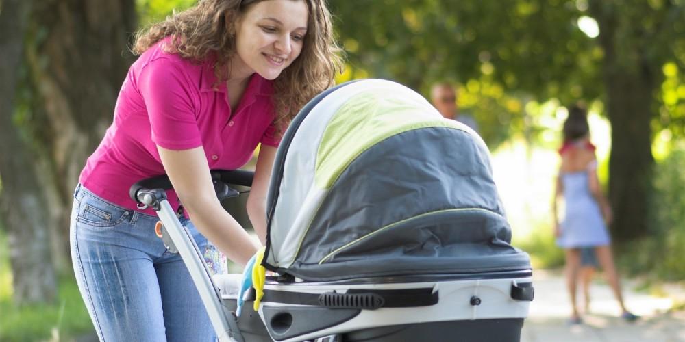 Junge Mutter mit Kinderwagen im Park