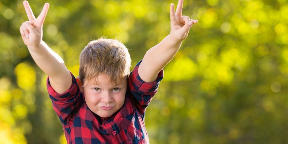 Junge in Holzfällerhemd macht das Victory-Zeichen