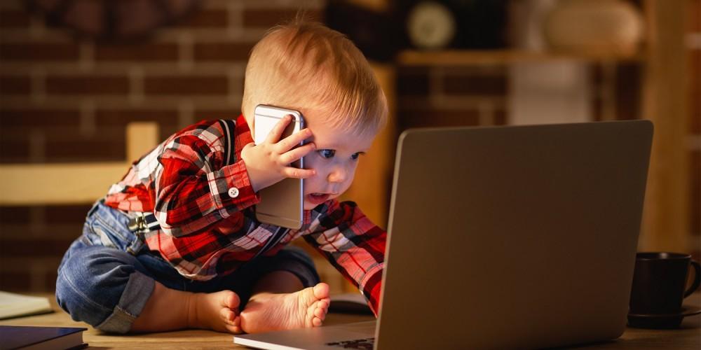 Kleiner Junge in rotem Karohemd und Jeans sitzt vor einem Laptop auf dem Tisch und hält ein Smartphone ans Ohr
