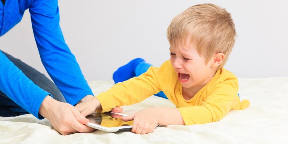 Schreiender Junge verteidigt den Tablet-PC