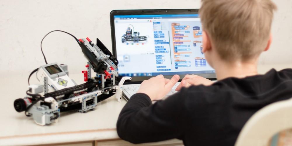 Junge arbeitet am PC mit einem gebauten Spielzeugroboter