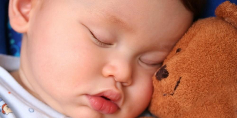 Gesicht eines Säuglings, schläft neben seinem Teddybären