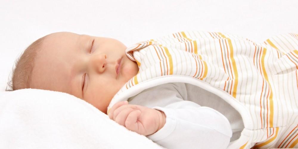 Baby schläft in Schlafsack auf dem Rücken