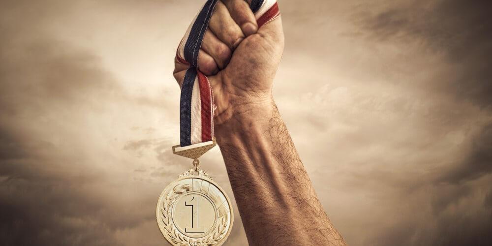 Zum Himmel gestreckter Arm mit Sieger-Medaille in der Hand