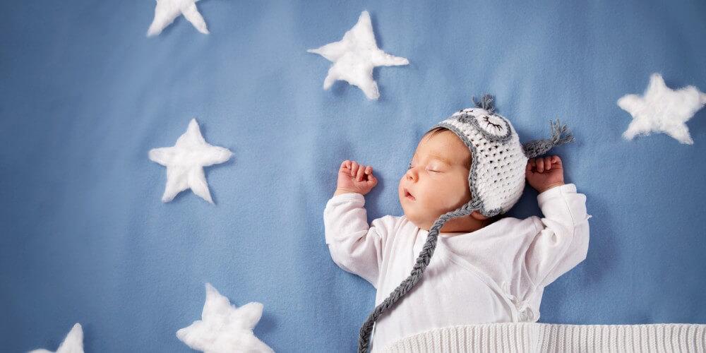 Baby mit Decke und Mütze schläft auf blauer Decke voller weißer Sterne aus Watte