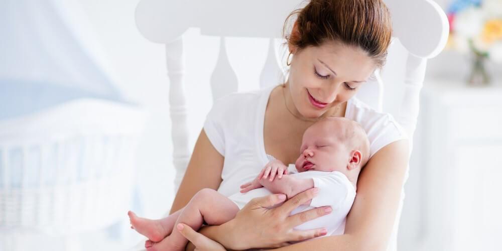 Mutter sitzt mit ihrem Baby im Arm in einem weißen Schaukelstuhl im Babyzimmer