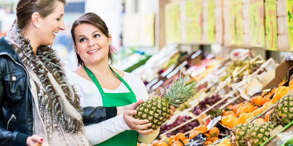 Schwangere Frau kauft Obst auf dem Markt