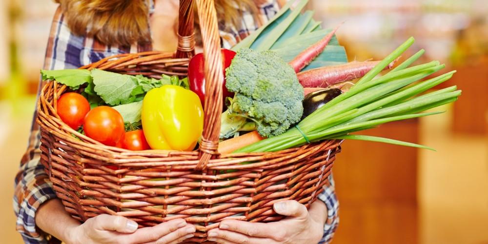 Frau mit Korb voller Gemüse im Supermarkt