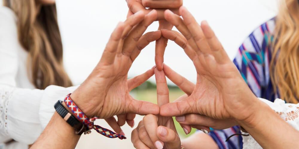 Sechs Hände einer Gruppe junger Hippies bilden mit den Fingern ein Peace-Zeichen