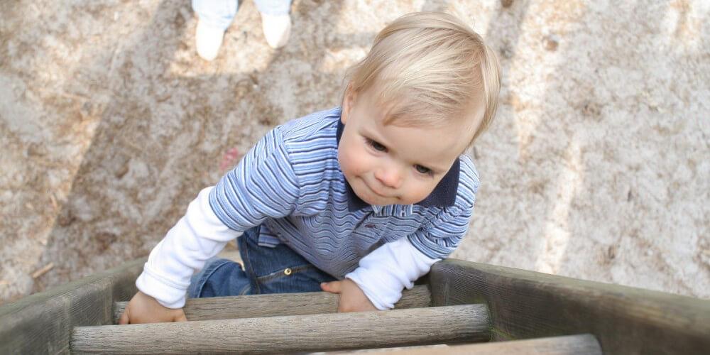 Aufnahme von oben, Kleinkind klettert Holzleiter hinauf, unten steht Mutter