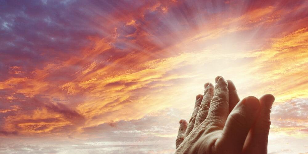Betende Hände unter dem Himmel