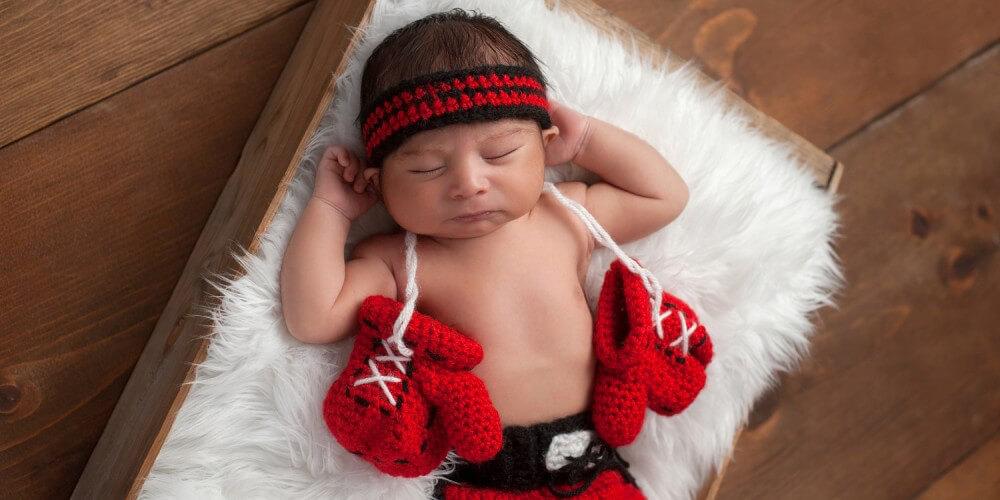 Baby liegt in gestrickten Boxer-Bekleidung und mit roten Woll-Boxhandschuhen auf einem Lammfell