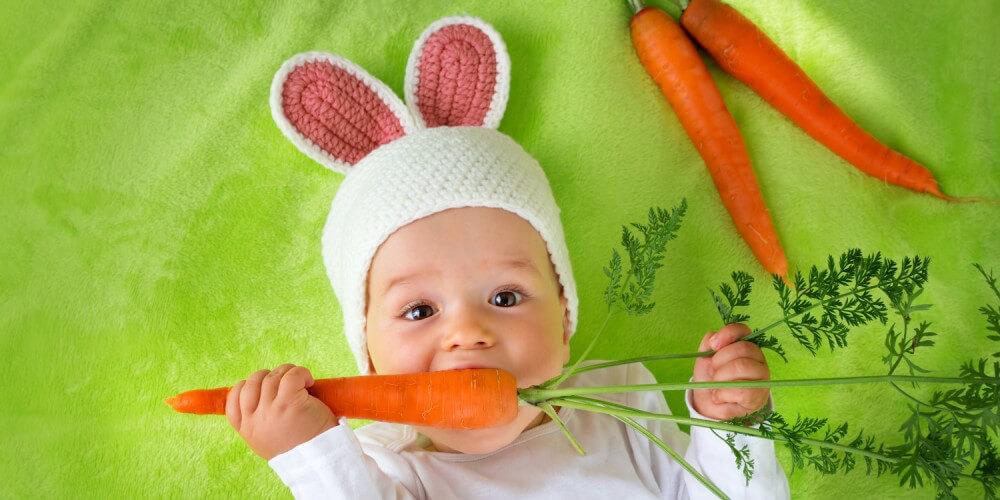 Baby liegt als Hase verkleidet neben zwei Möhren auf einer grünen Decke und beißt in eine Möhre