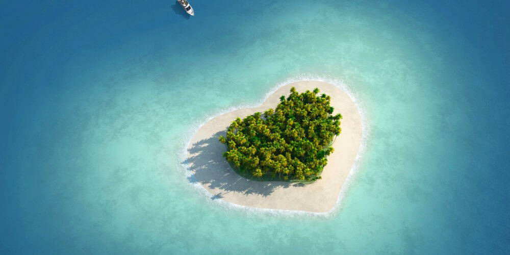 Winzige Insel in Form eines Herzens wird von einem Boot angefahren, Blick von oben
