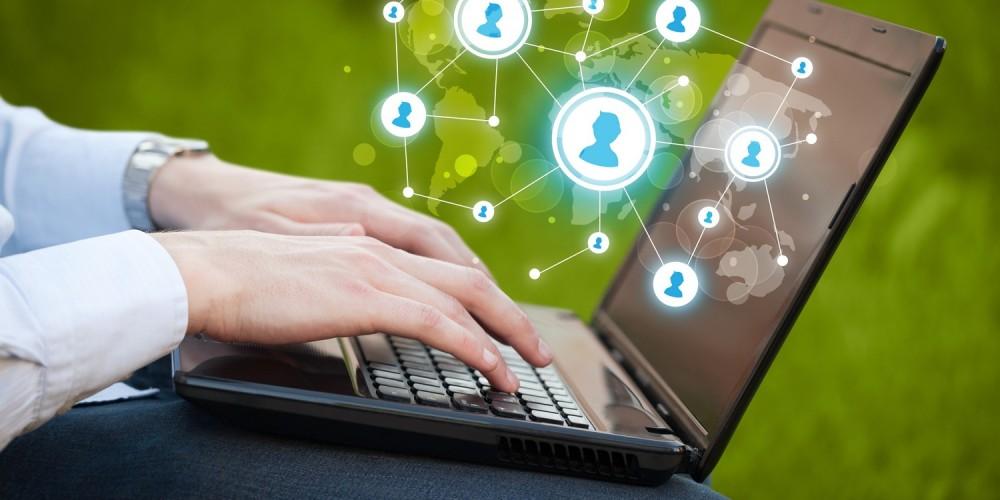 Mann sitzt am Laptop und surft in Sozialen Medien