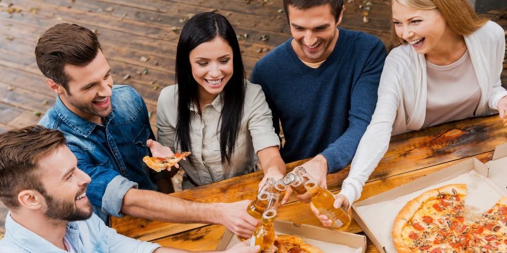 Freunde stoßen gemeinsam an und essen Pizza