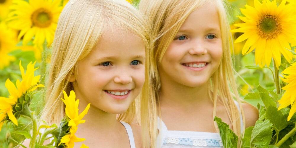 Zwei blonde Mädchen stehen lächelnd in einem Sonnenblumenfeld
