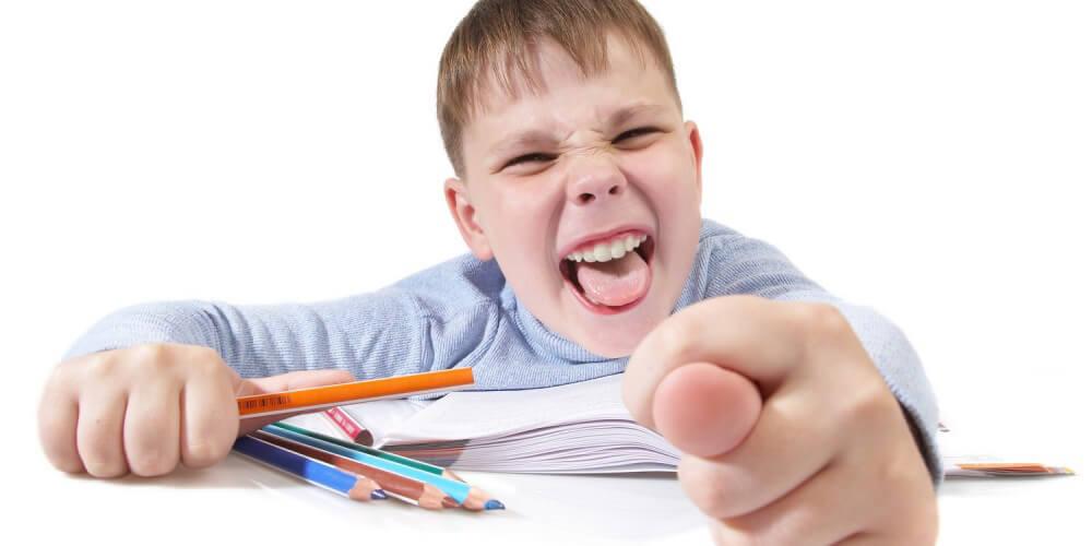 Kleiner Junge mit Buch und Buntstiften grinst mit offenem Mund frech in die Kamera