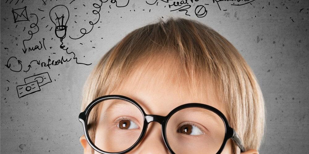 Blonder Junge mit großer runder Hornbrille blickt nach oben zu einer Ansammlung von kleinen Zeichnungen (Fotomontage)
