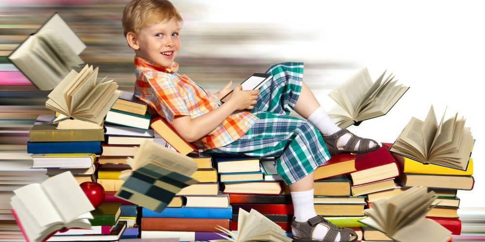 Junge sitzt auf einem Bücherberg