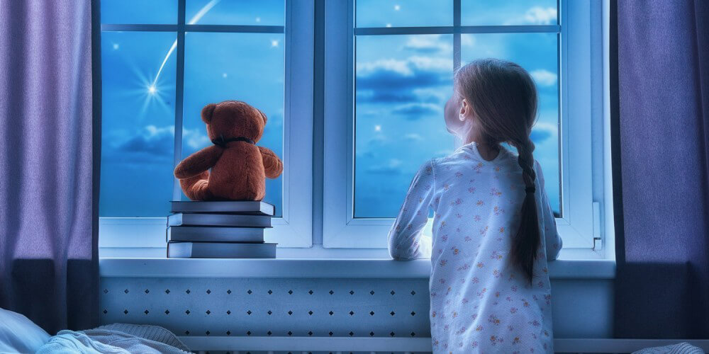 Kleines Mädchen sitzt in ihrem Bett und guckt aus dem Fenster, Sternschnuppe am Himmel