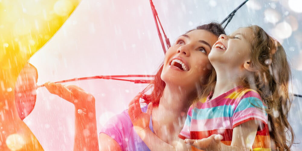 Mutter und Tochter stehen mit großem bunten Schirm lachen im Regen
