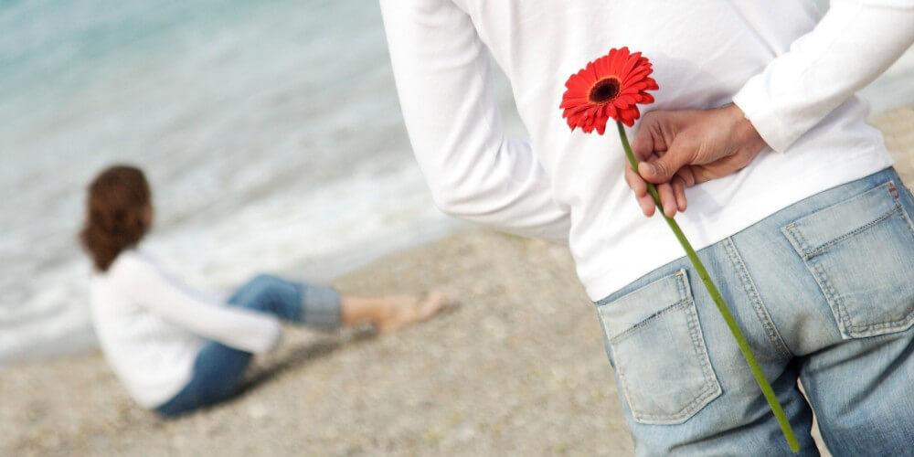 Mann überrascht Frau mit Blume am Strand