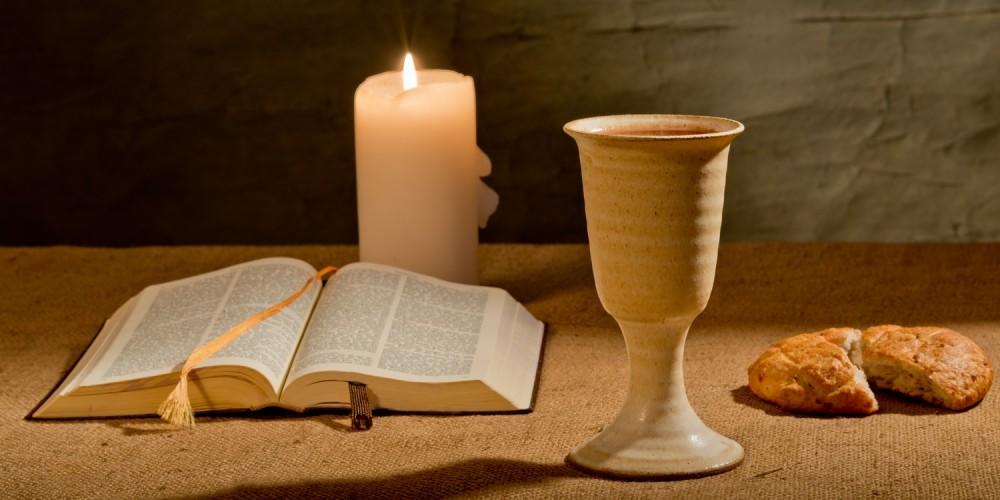 Bibel, Kerze, Kelch und Brot