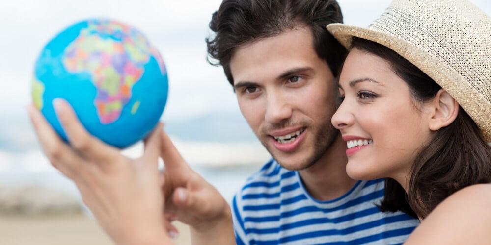Junges Paar am Strand, sie trägt einen Hut und zeigt auf einen kleinen Globus
