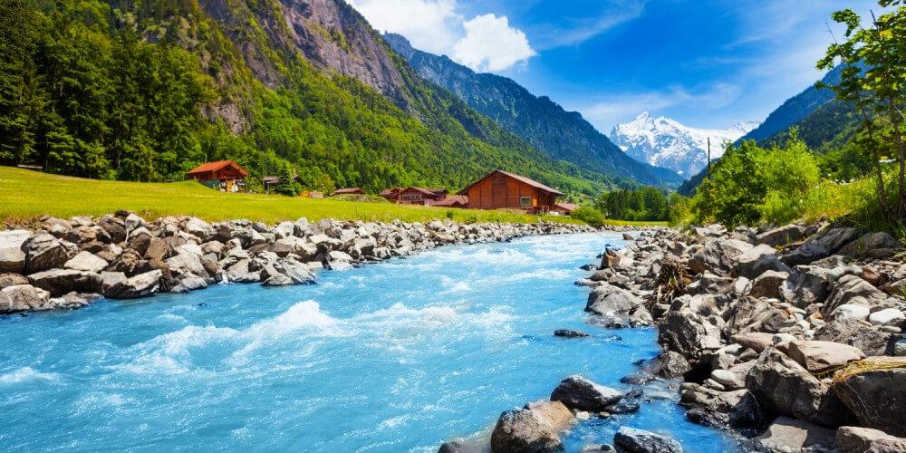 Fließender Bach/Fluss in einem schweizer Gebirge, im Hintergrund Häuser und Berge