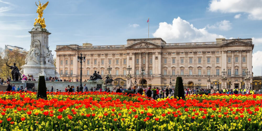 Buckingham Palace in London hinter leuchtend rot-gelben Blumenbeeten