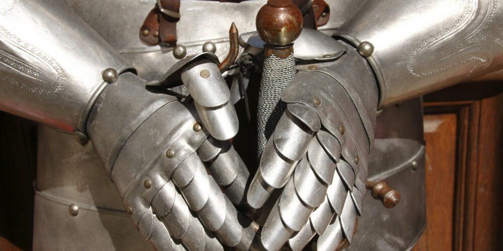 Historische Ritterrüstung, die Hände halten einen Schwertknauf