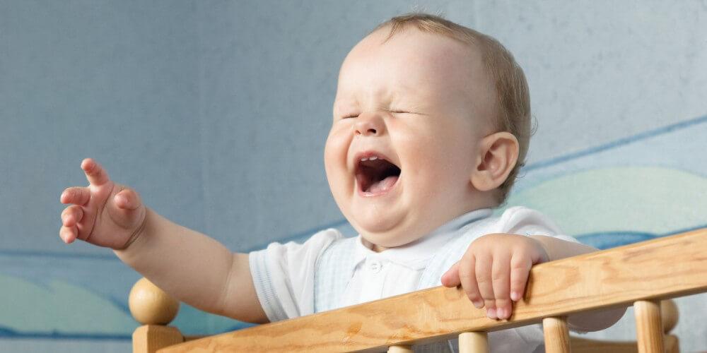 Baby steht im Babybett und schreit, streckt Hand nach Mutter aus