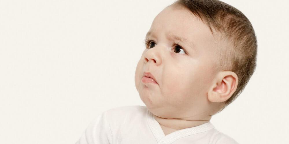 Dunkelhaariger Baby-Junge in weißem Body guckt angeekelt zur Seite